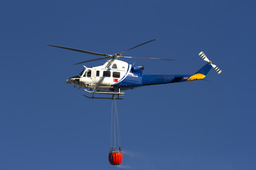 Helicóptero de extinción de fuegos de montes, dirigiéndose a un fuego derramando agua de una canasta que transporta