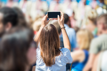 Young woman with smartphone in a hand taking picture in crowd of people