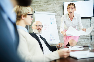 Irritated young businesswoman with one knee on table having argument with colleague at briefing
