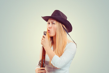 Confident woman blowing at gun after shooting