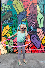 young girl with hula hoop and sunglasses