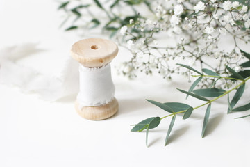 Feminine floral scene. Close-up of spool of silk ribbon, Eucalyptus parvifolia leaves and babys breath Gypsophyla flowers on a white table background. Wedding styled stock photography. Selective focus