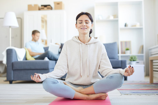 Cheerful cross-legged young woman sitting in pose of lotus on the floor of living-room