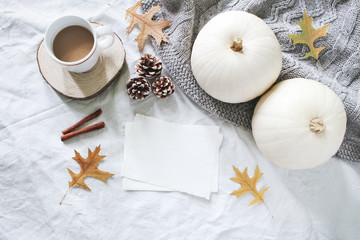 Autumn breakfast in bed composition. Blank cards mockup. Cup of coffee, white pumpkins, sweater, oak leaves and pine cones on linen background. Thanksgiving, Halloween. Flat lay. Top view.