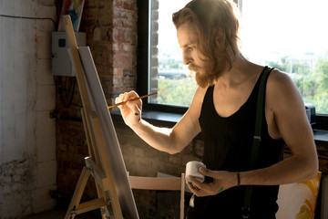 Side view portrait of focused long haired artist holding brush and painting on easel in art studio lit by sunlight, copy space