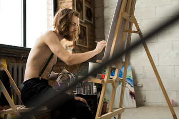 Side view portrait of shirtless male artist drawing sketches while sitting by easel in loft like art studio, copy space