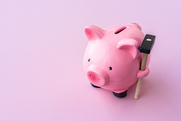 Top view of pink piggy bank with hammer on pink background.