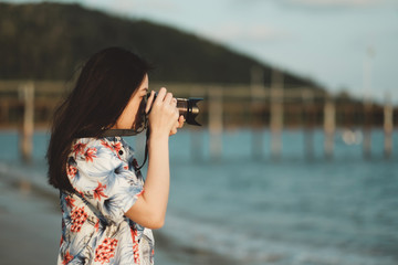 Young asian woman holding vintage camera with beach view in sunset light.