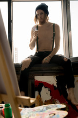 Full length portrait of contemporary male artist smoking cigarettes while sitting on window in art studio