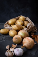 Potato, onion, garlic. Ingredients on the table and dark background.