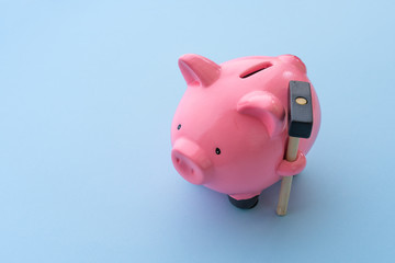 Top view of pink piggy bank with hammer on blue background.