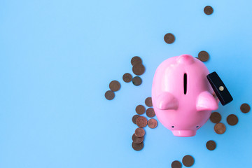 Top view of pink piggy bank with hammer and coins on blue background.