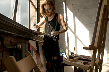 Portrait of handsome male artist painting picture standing by window art studio lit by sunlight, copy space