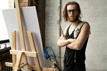 Waist up portrait of contemporary long haired artist looking away pensively while standing by easel in art studio, copy space