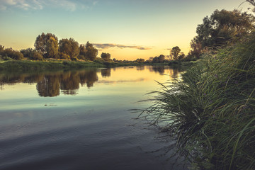 Summer season rustic countryside calm river landscape sunset with clear sky reflections riverbank in vintage style