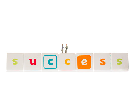 Word Success made from wooden cubes with miniature businessmen handshaking isolated on white background. Business concept.