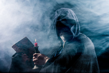 Obraz a mysterious figure holds a book and a candle in his hands - fototapety do salonu
