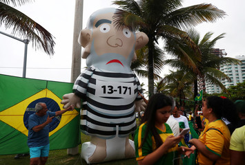 Supporters of Bolsonaro, far-right lawmaker and presidential candidate of the PSL, stand next to an inflatable doll depicting former Brazilian president Lula da Silva, in Rio de Janeiro