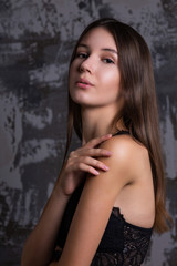 Test shoot of elegant brunette girl with perfect skin posing in a black lace bra against grey wall
