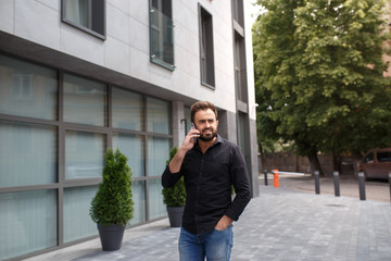 A man with a beard goes and speaks by phone