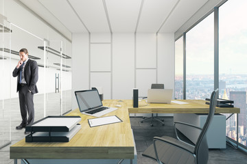 Attractive businessman in clean office interior