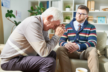 Sad emotional senior patient sitting on sofa and leaning on hands while crying during psychotherapy session, attentive psychiatrist listening to him