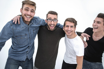 Four cheerful young guys stand and hug