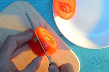 chopping a tomato on a cutting board on a blue-turquoise table near white ceramic plate