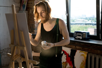 Waist up portrait of long haired male artist painting on easel while enjoying work in art studio lit by sunlight, copy space