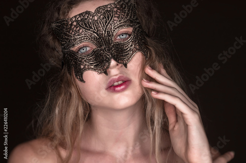Beautiful young tender woman posing isolated over dark beige chocolate  brown background wall wearing carnival cat masquerade mask looking camera. b07372058d9
