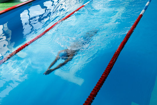 Image of sportsman in blue cap swimming on path in pool during workout