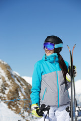 Photo of young smiling female athlete looking away in helmet with skis in hand against blue sky and snowy hill