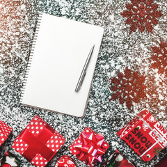 View from above, top, flat, on Xmas present boxes, package, decorative handmade snowflakes, with space for text in notepad with pen, on gray, stone, marble background, motivation greeting card.