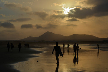 silhouettes of people on the sandy shore of the ocean at sunset