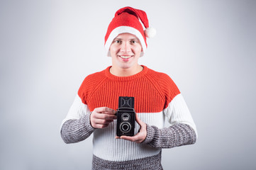 Santa Claus taking picture with old camera.