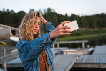 Young woman making selfie on coast of lake