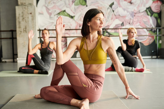 Full length portrait of female yoga instructor showing poses to class during fitness session, copy space