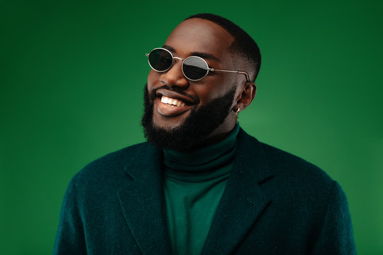 Man portrait. Style. Handsome Afro American guy in green jacket and sun glasses is looking at camera and smiling, on a green background