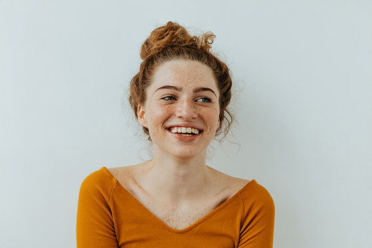 Woman portrait. Happiness. Beautiful blue eyed girl with freckles is looking away and laughing, on a white background