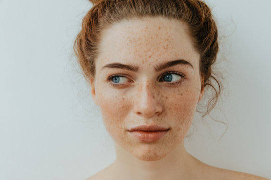 Woman portrait. Close-up. Beautiful blue eyed girl with freckles is looking away, on a white background