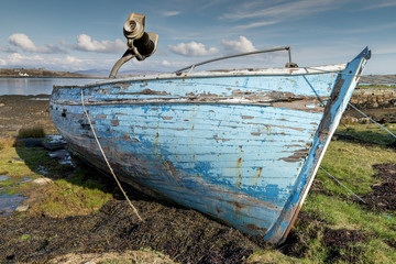 Derelict fishing boat, left to decay on the beach, Roundwood Ireland. Wooden - Blue