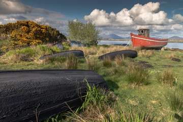 Derelict fishing boats , left to decay on the beach, Roundwood Ireland. Wooden - Red