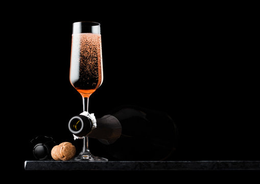 Elegant glass of pink rose champagne with cork and wire cage and bottle on black marble board on black background. Space for text