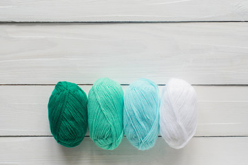 knitting clew in row on white wooden background, pastel green and white colors, top view flat lay with copy space, stock photo image