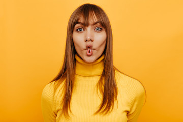 Making faces. Cheerful young woman is grimacing at camera, on a yellow background