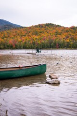 A canoe and adirondack chair on a lake surrounded by fall color in New England