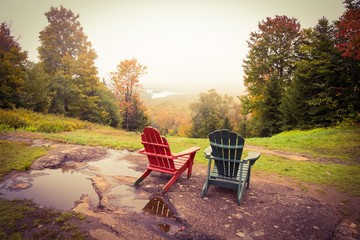 Two empty adirondack chairs overlook a foggy valley with fall color