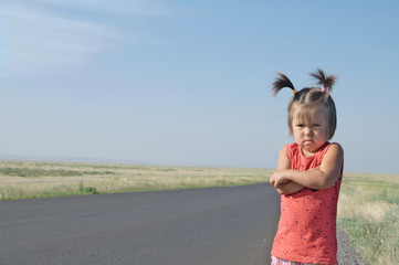 resentful child is standing and don't want to go anywhere defend own position . Little girl in kazakh steppe, cute adorable kid. Relationships with kids concept