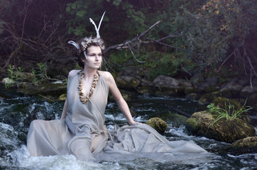 river nymph in a gray silk dress, a necklace of sea snail shells and a headdress of perevsidit and resting in his river