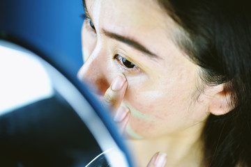 Asian woman applying cosmetics makeup and using color correction concealer, Learning doing self makeup.